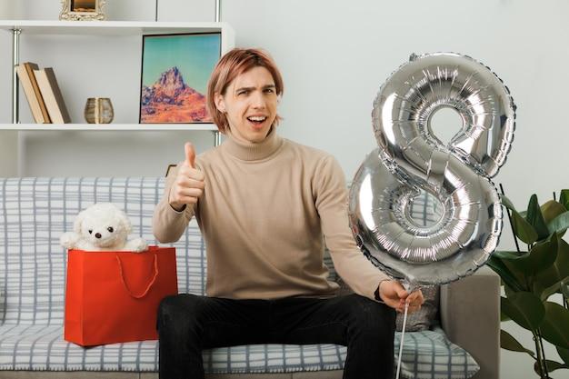 Sorrindo, mostrando o polegar para o cara bonito no dia da mulher feliz segurando o balão número oito sentado no sofá da sala de estar