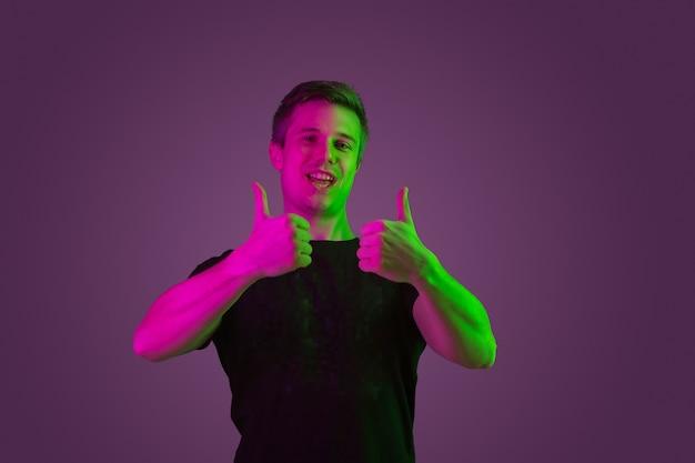 Sorrindo, mostrando os polegares para cima. retrato do homem caucasiano sobre fundo roxo studio em luz de néon. lindo modelo masculino de camisa preta. conceito de emoções humanas, expressão facial, vendas, anúncio.