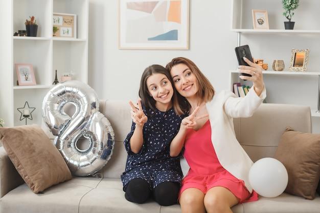 Sorrindo, mostrando um gesto de paz, filha e mãe no feliz dia da mulher, sentada no sofá, tirando uma selfie na sala de estar