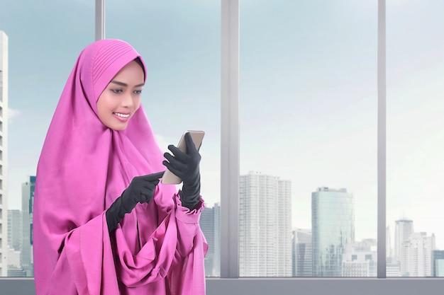 Sorrindo, muçulmano asiático, mulher, messaging, ligado, a, telefone móvel