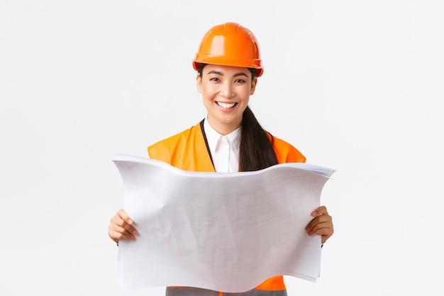 Sorrindo muito asiática arquiteta feminina, mulher industrial com capacete de segurança e jaqueta reflexiva, ficar satisfeita depois de ler plantas, construir casas, construir algo, parede branca.