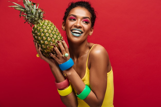 Sorrindo mulata com maquiagem moda na camisa amarela, desfrutando de vitamina natural, segurando nas mãos abacaxi maduro fresco isolado, sobre parede vermelha