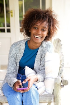 Sorrindo, mulher africana, sentando, com, cellphone