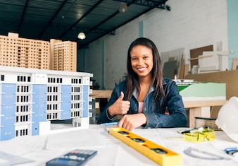 Sorrindo, mulher africano-americana, mostrando, polegar cima, perto, modelo, de, predios