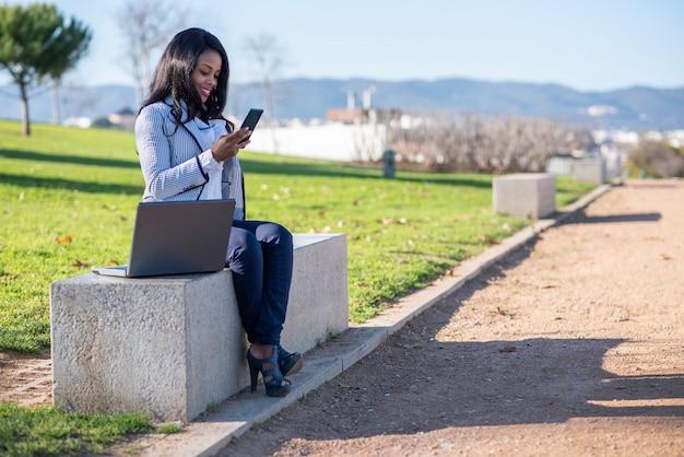 Sorrindo mulher afro-americana em um banco usando um laptop e telefone celular em um parque ao ar livre