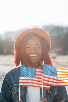 Sorrindo, mulher americana africana, com, bandeiras americanas