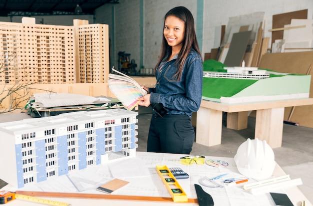 Sorrindo, mulher americana africana, mostrando, exemplos, de, cores, perto, tabela, com, equipamentos