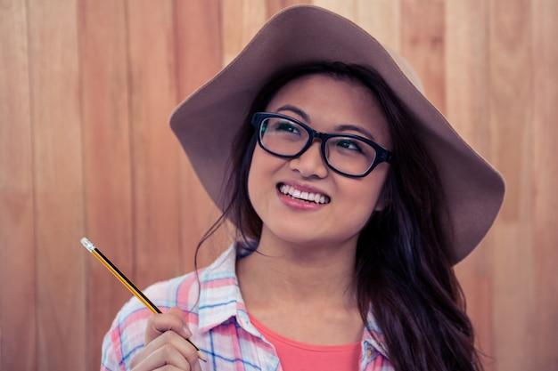 Sorrindo, mulher asian, com, chapéu, segurando, lápis, contra, parede madeira