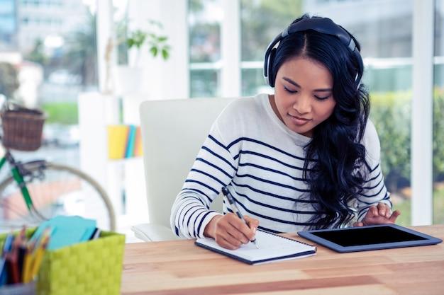 Sorrindo mulher asiática com fones de ouvido, escrevendo no bloco de notas no escritório