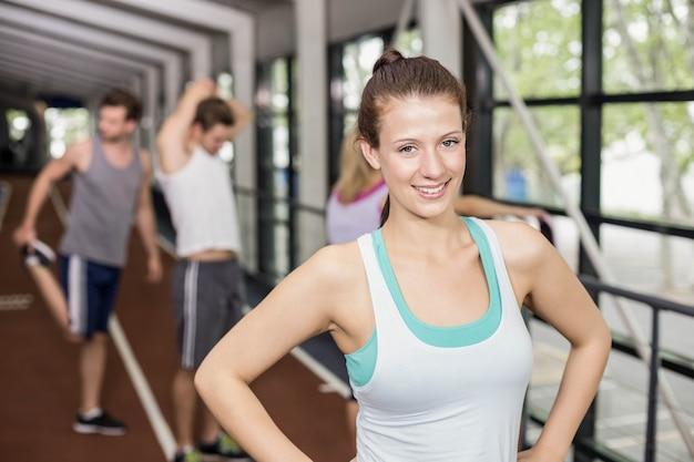 Sorrindo mulher atlética posando com as mãos nos quadris na pista