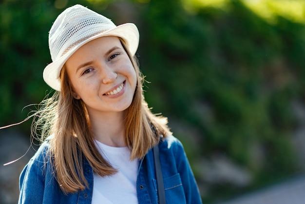 Sorrindo, mulher bonita, em, a, chapéu, e, casual, roupas modestas, olhar, a, câmera