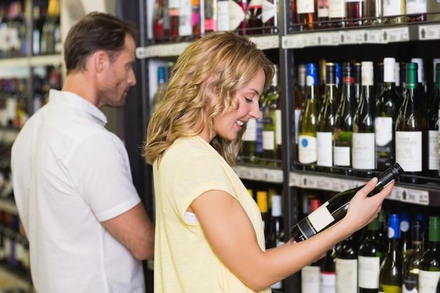 Sorrindo, mulher bonita, olhando garrafa de vinho