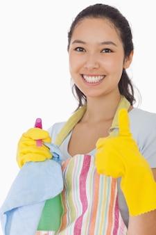 Sorrindo mulher com produtos de limpeza dando polegares para cima