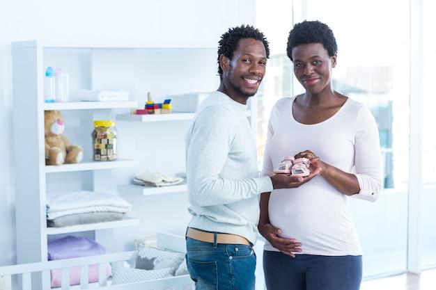 Sorrindo, mulher, dar, sapatos bebê, para, dela, marido, enquanto, ficar, casa