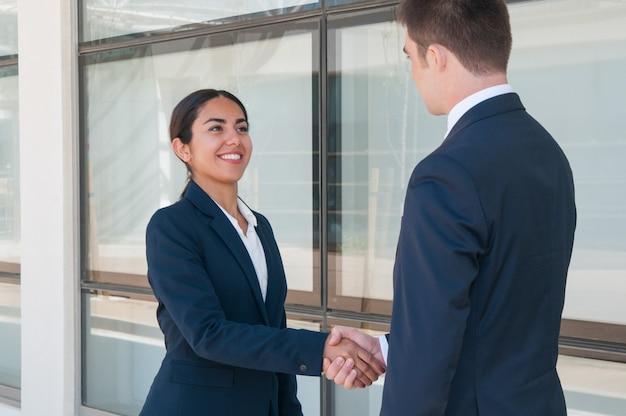 Sorrindo mulher de negócios ambicioso dizendo adeus ao parceiro