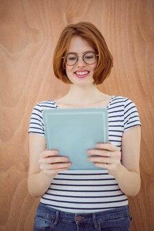 Sorrindo mulher de negócios hipster em um computador tablet, contra uma madeira