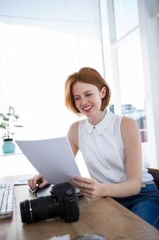 Sorrindo mulher de negócios hipster sentado em seus arquivos de leitura de mesa