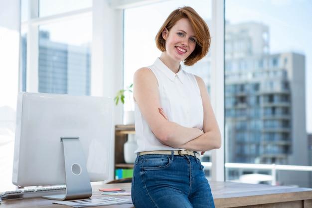 Sorrindo mulher de negócios hipster sentado em sua mesa com os braços cruzados