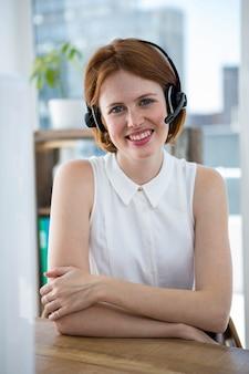 Sorrindo mulher de negócios hipster, sentado em sua mesa em um fone de ouvido sem fio