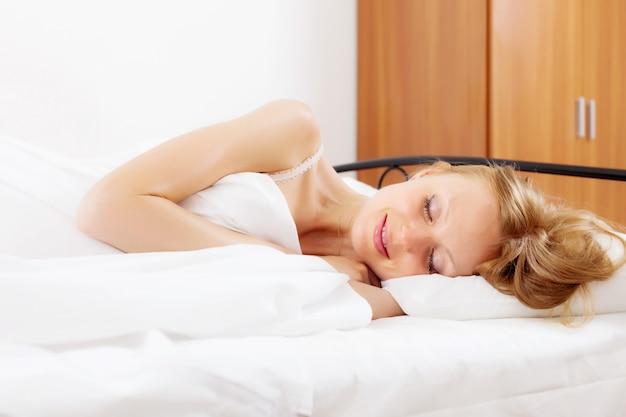 Sorrindo mulher dormindo na cama