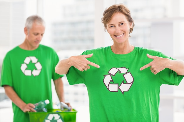 Sorrindo mulher eco-mental mostrando sua camisa de reciclagem