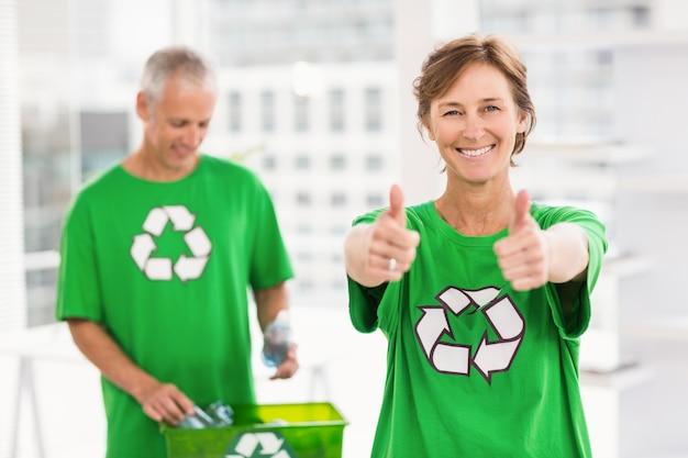 Sorrindo mulher eco-minded fazendo polegares para cima