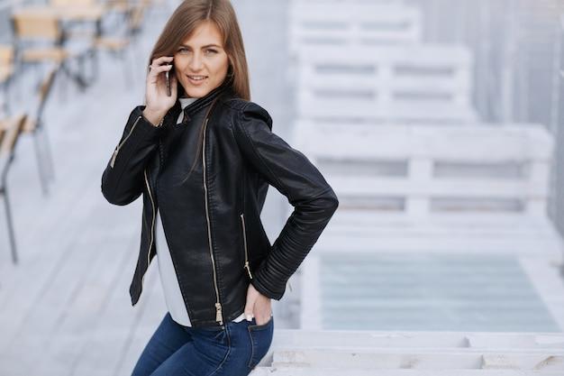 Sorrindo mulher, falando sobre um telefone móvel com uma mão no bolso