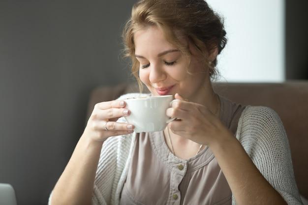 Sorrindo mulher feliz bebendo café aromático com olhos fechados