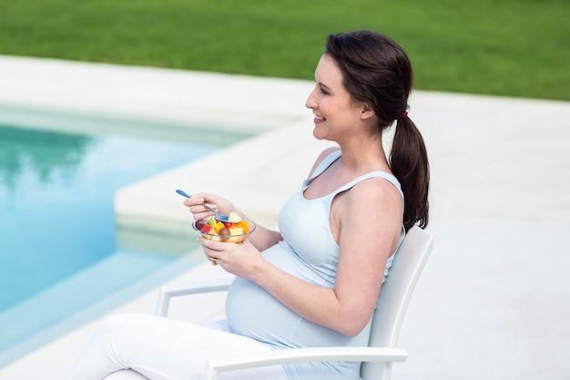 Sorrindo, mulher grávida, comer, fruta, perto, piscina