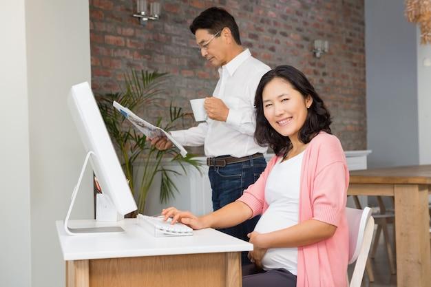 Sorrindo, mulher grávida, usando computador portátil, enquanto, marido, é, leitura, jornal
