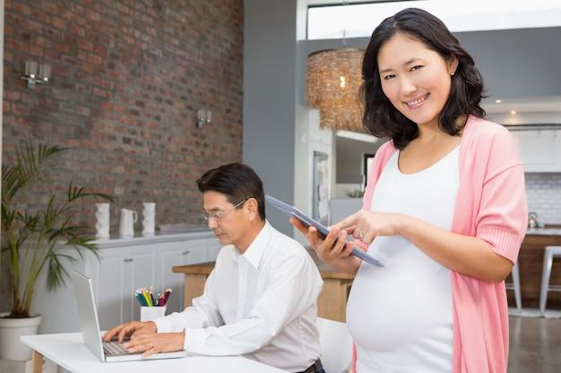 Sorrindo, mulher grávida, usando, tabuleta, casa, enquanto, marido, é, trabalhando, ligado, laptop1
