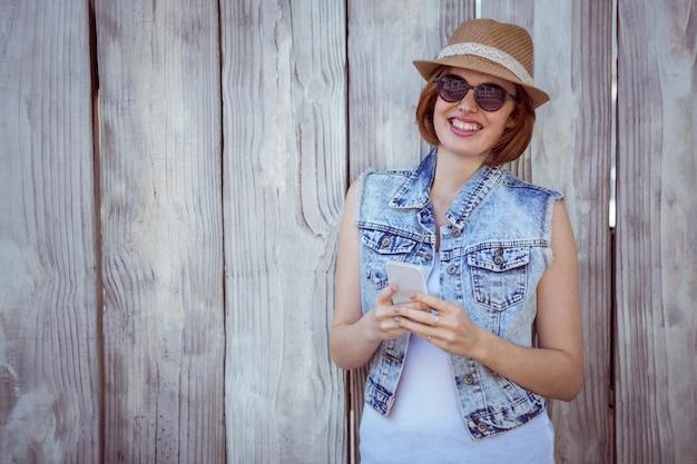 Sorrindo mulher hipster em seu smartphone