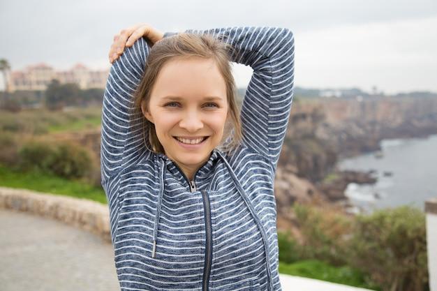 Sorrindo, mulher jovem, aquecer, corporal, antes de, treinamento ao ar livre
