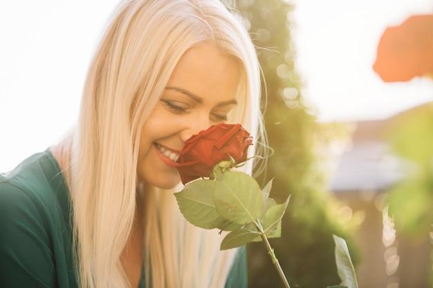 Sorrindo, mulher jovem bonita, cheirando, rosa vermelha