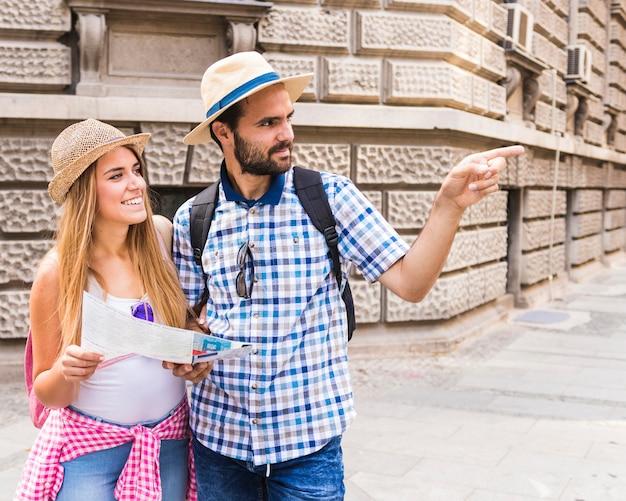 Sorrindo, mulher jovem, com, mapa, olhar, homem, mostrando, direção