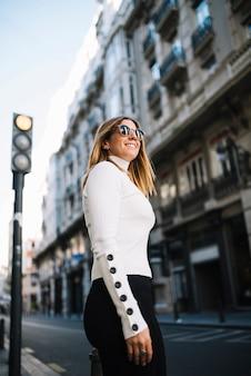 Sorrindo, mulher jovem, com, óculos de sol, perto, estrada, em, cidade