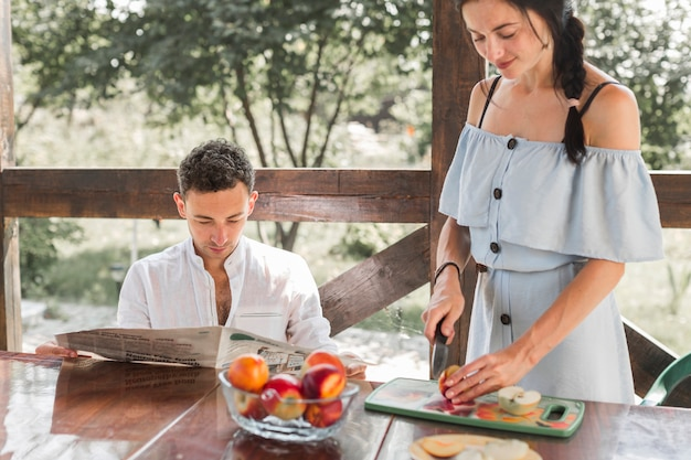 Sorrindo, mulher jovem, corte, frutas, com, dela, marido, jornal leitura