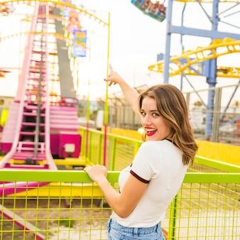 Sorrindo, mulher jovem, dedo apontando, em, montanha-russa, passeio