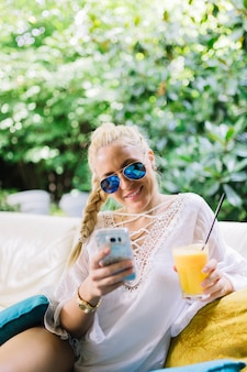 Sorrindo, mulher jovem, desgastar, elegante, óculos de sol, copo segurando, de, suco