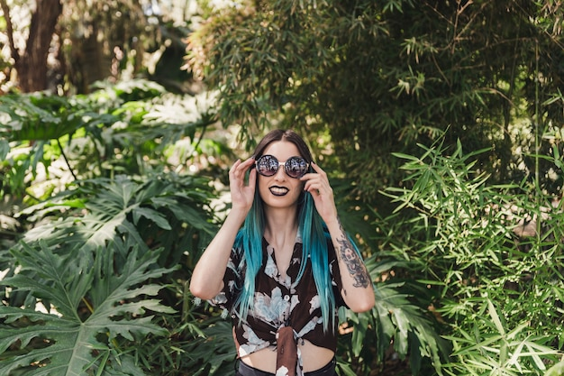 Sorrindo, mulher jovem, desgastar, óculos de sol, ficar, entre, árvores