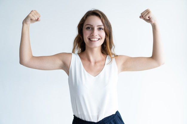 Sorrindo mulher jovem e bonita levantando as mãos cerradas