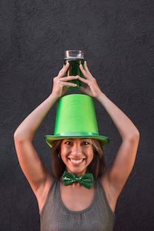 Sorrindo, mulher jovem, em, são, patricks, chapéu, copo segurando, de, bebida