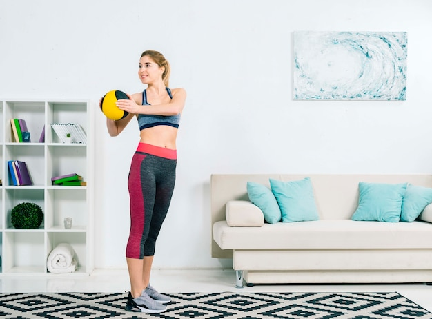 Sorrindo, mulher jovem, em, sportswear, exercitar, com, bola médica, em, a, sala de estar