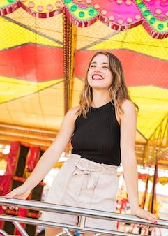 Sorrindo, mulher jovem, estar, atrás de, a, trilhos, em, parque divertimento