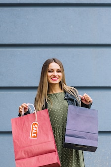 Sorrindo, mulher jovem, ficar, contra, parede, segurando, roxo, e, vermelho, bolsas para compras
