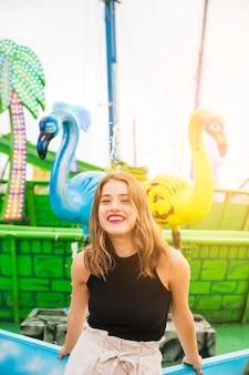 Sorrindo, mulher jovem, ficar, frente, chafariz, em, parque divertimento