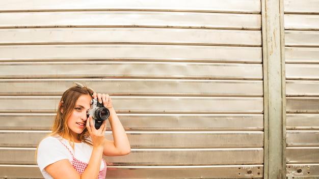 Sorrindo, mulher jovem, ficar, frente, obturador, porta, levando, foto, com, câmera