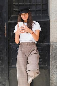 Sorrindo, mulher jovem, ficar, frente, pretas, pintado, parede, texting, mensagem, ligado, smartphone