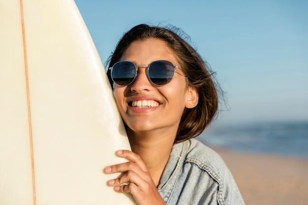 Sorrindo, mulher jovem, ligado, praia, com, surfboard