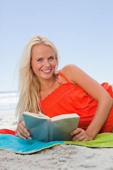 Sorrindo, mulher jovem, mentindo, ao lado, enquanto, leitura um livro